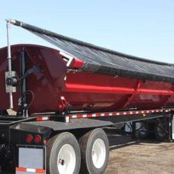 Aero Side Kick 2 side dump tarp system with a black mesh tarp, installed on a maroon side dump trailer.