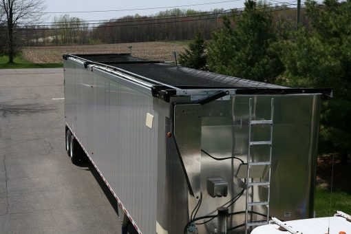 Aero Lid 2, tarping system installed on an aluminum refuse trailer, tarp is in the closed position.