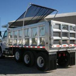 Donovan Flash electric flip tarp system installed on an aluminum tri axle dump truck with the tarp deploying over the load.