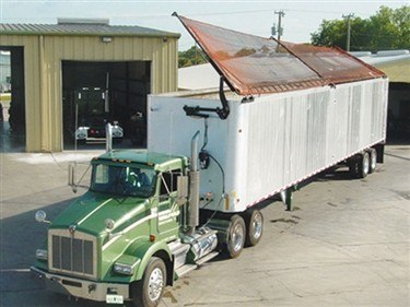 Donovan Sidwinder transfer trailer tarp system in operation on a walking floor trailer.