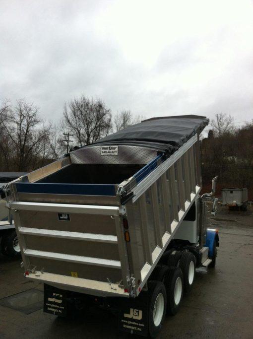 Merlot's cable drive Smart Tarp system half way open on a tri axle dump truck.