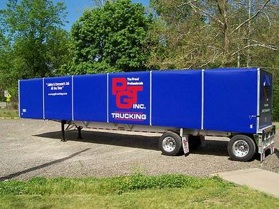 Merlot VanGo rolling tarp system on a flat bed trailer with blue vinyl tarp panels.