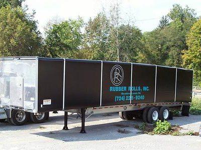 Merlot VanGo folling tarp system on a flat bed trailer with black vinyl tarp panels.