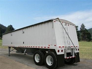 Shur Co, Shur-Lok side roll tarp system with a black vinyl tarp covering a white grain trailer.
