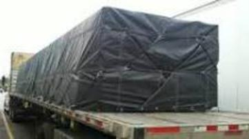 Lumber tarp covering a load on a flat bed trailer.
