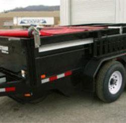 Manual pull style tarp system with red tarp on a black dump trailer.