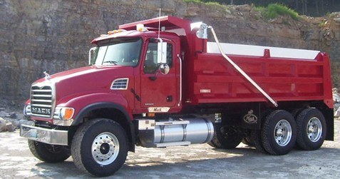 Patriot electric flip tarp system on a red tandem axle dump truck.