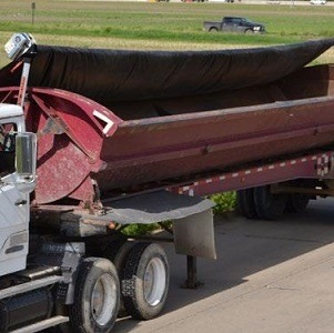 Mountain Tarp, Smooth Roll, Side Dump Tarp System on a Red Trailer