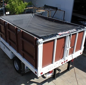 Pulltarps Open System on a single axle flat bed truck.