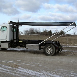 Roll-Rite DC200 Auto Tarper on a Hook Lift Roll-Off Truck with the tarp deployed
